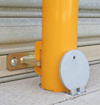 Removable bollard secured to roller door